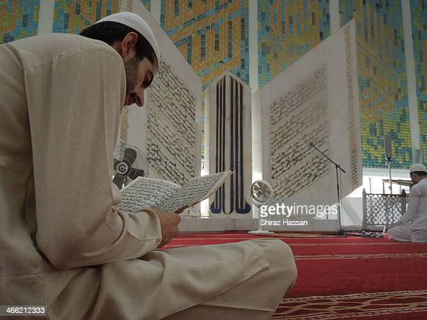 CONTENT] A man is reciting Quran at Faisal Mosque Islamabad Pakistan