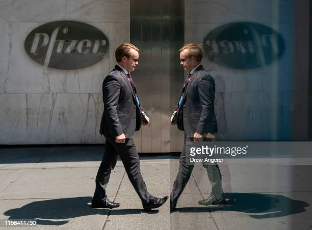 A man is reflected in a bus stop window as he walks past Pfizer world headquarters in Midtown Manhattan on July 29 2019 in New York City On Monday...