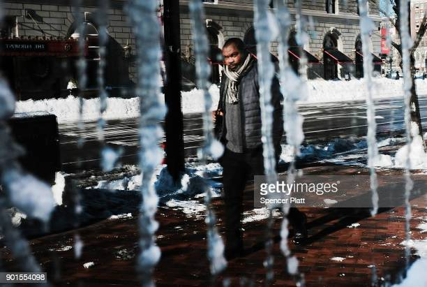 A man is reflected in a frozen window the morning after a massive winter storm on January 5 2018 in Boston United States Schools and businesses...