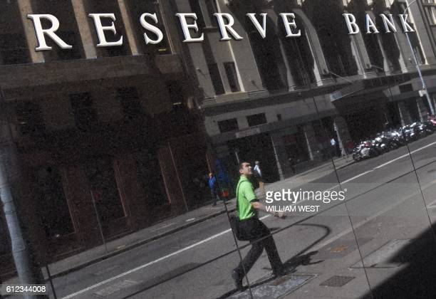 A man is reflected in a wall beneath the Reserve Bank of Australia sign in Sydney on October 4 as Australia's central bank kept interest rates at a...