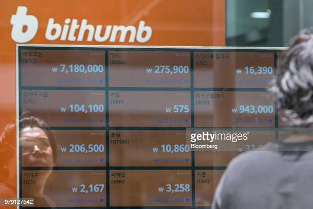 A man is reflected in a window as he looks at monitors displaying the prices of cryptocurrencies at a Bithumb exchange office in Seoul South Korea on...