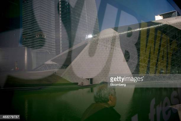 Man is reflected in an advertisement for the Subway restaurant chain in the Zhujiang New Town district of Guangzhou, China, on Friday, Nov. 29, 2013....
