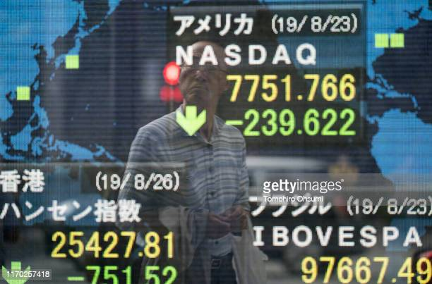 Man is reflected in an electronic stock board outside a security firm on August 26, 2019 in Tokyo, Japan. Japanese stocks dropped and the yen climbed...