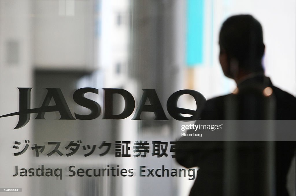 A man is reflected in the Jasdaq Securities Exchange Inc. logo in ...