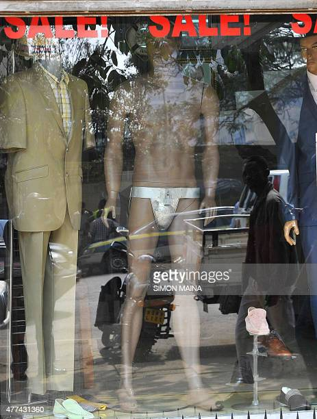 A man is reflected looking at the window of a men's clothing shop next to a mannequin wearing a chastity belt with an iron padlock on sale for 20 USD...