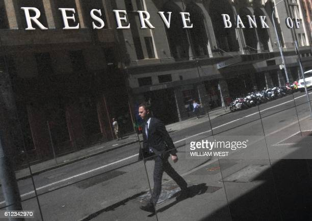 A man is reflected on a wall underneath the Reserve Bank of Australia sign in Sydney on October 4 as Australia's central bank kept interest rates at...