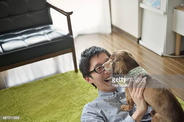 A man is relaxing in the room and pet dog