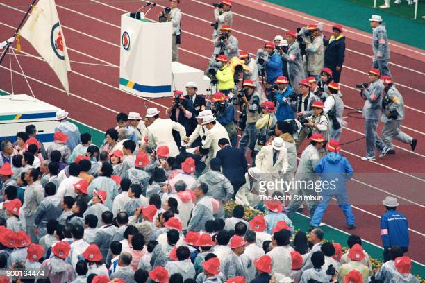A man is removed by security staffs as he tries to throw a smoke bomb toward Emperor Akihito and Empress Michiko during the opening ceremony of the...