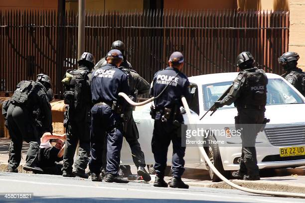 A man is removed from his vehicle by tactical police outside NSW Parliament House on Macquarie Street on December 20 2013 in Sydney Australia The NSW...