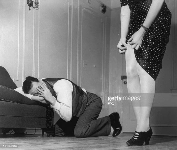 A man is rendered helpless as he peeks through his fingers at a woman adjusting her suspenders circa 1940
