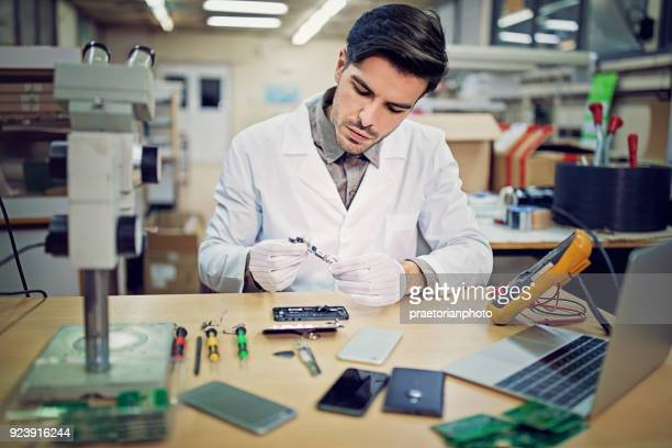 man is repairing a mobile phone in the service - symbol stock pictures, royalty-free photos & images