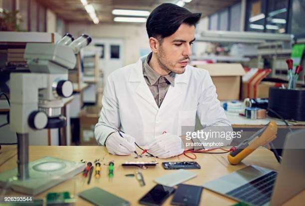 Man is het repareren van een mobiele telefoon in de dienst