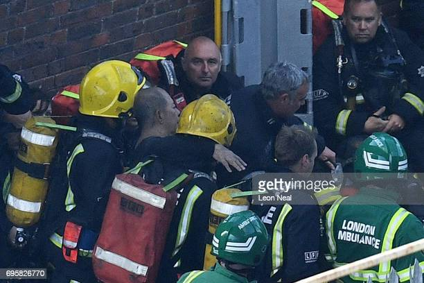 A man is rescued by fire fighters after a huge fire engulfed the 24 storey residential Grenfell Tower block in Latimer Road West London in the early...