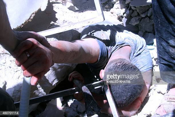 A man is rescued from under the rubble after Syrian regime helicopters allegedly dropped barrel bombs on the Sukkari neighbourhood an oppositionheld...