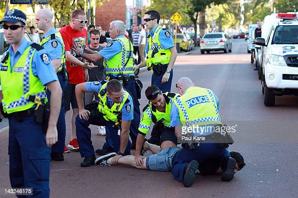 A man is restrained by police officers after trouble broke out between fans at the Elephant and Wheelbarrow pub after the ALeague Grand Final between...