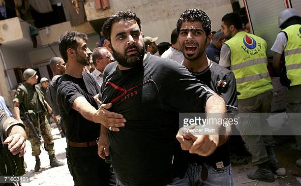 Man is restrained the morning after a building collapsed due to an Israeli attack August 8, 2006 in Beirut, Lebanon. The evening target was the...
