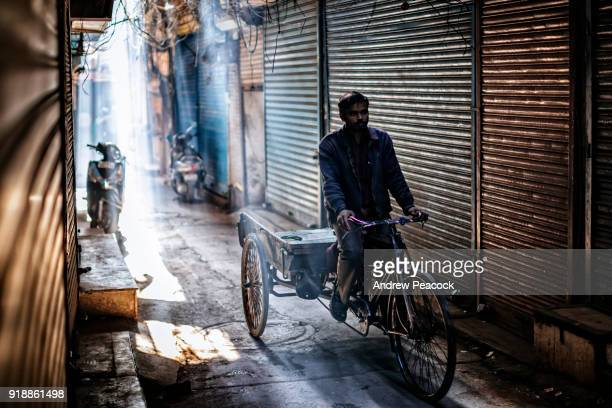 A man is riding down a deserted laneway on a bicycle with cart.