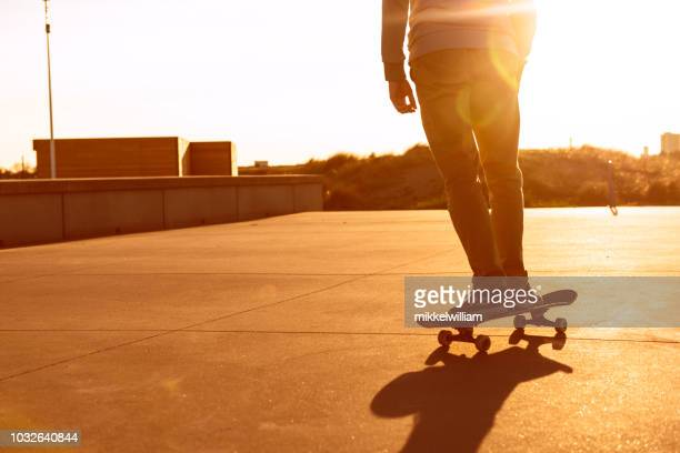 Man is riding skateboard as the sun sets in the horizon