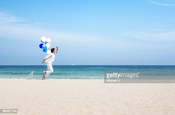 A man is running on the beach with the balloon.