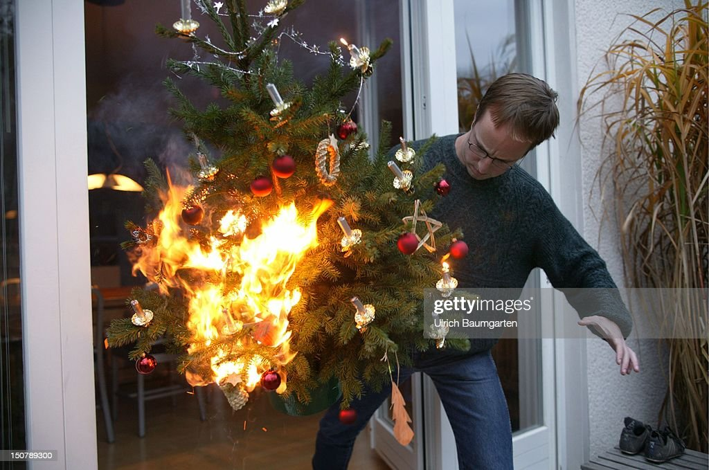 Burning Christmas Tree.Man Is Running With A Burning Christmas Tree Out Of The