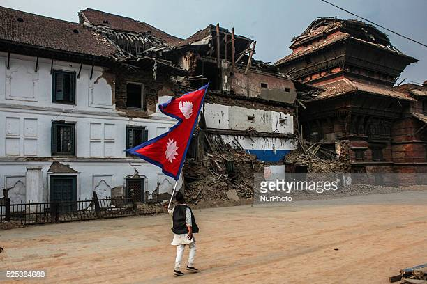 A man is running with a flag to rise up Nepali people as they are down due to the earthquake at Basantpur Durbar Square Katmandu Nepal 7 May 2015