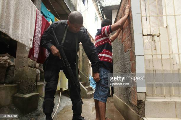 A man is searched by a member of Special Police Operations Battalion while they search homes for guns and drugs in the slum or favela Cantagalo in...