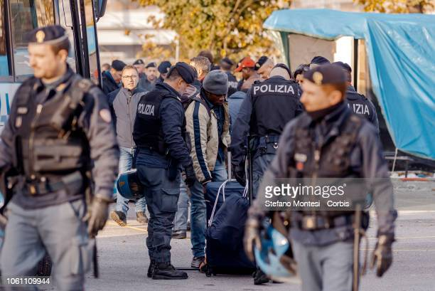 A man is searched by police as migrants board buses to transport them away from the makeshift migrants' camp known as 'The Baobab on November 13 2018...