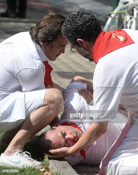 A man is seen after he hit his head on the pavement when he fell down during the opening day or 'Chupinazo' of the San Fermin Running of the Bulls...