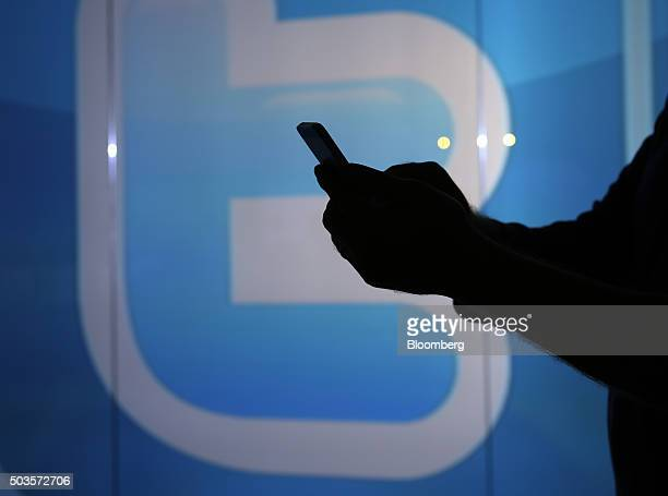 A man is seen as a silhouette as he checks a mobile device whilst standing against an illuminated wall bearing Twitter Inc's logo in this arranged...