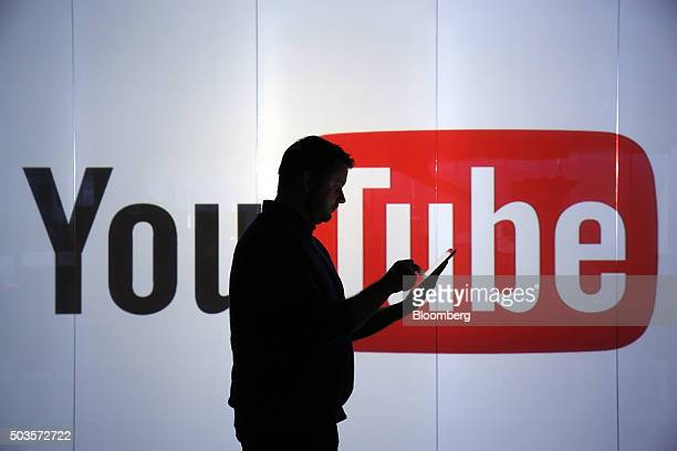 A man is seen as a silhouette as he checks a mobile device whilst standing against an illuminated wall bearing YouTube Inc's logo in this arranged...