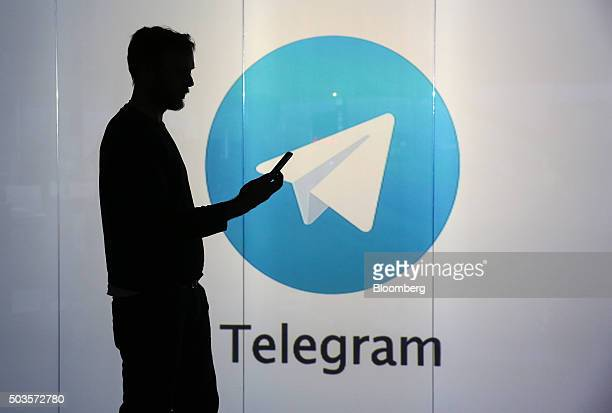 A man is seen as a silhouette as he checks a mobile device whilst standing against an illuminated wall bearing Telegram's logo in this arranged...