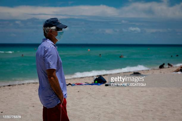 Man is seen at the beach wearing a facemask in Miami Beach, Florida on June 16, 2020. - Florida is reporting record daily totals of new coronavirus...