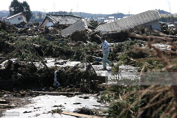 A man is seen at tsunami hit Minamisoma City on March 12 2011 in Minamisoma Fukushima Japan An earthquake measuring 89 on the Richter scale has hit...