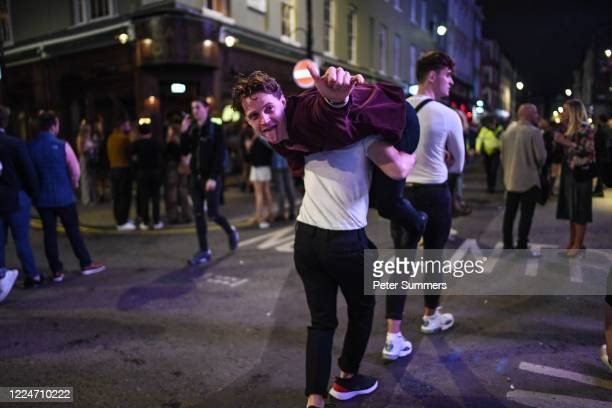 Man is seen being carried on his friend's shoulders in Soho on July 4, 2020 in London, United Kingdom. The UK Government announced that Pubs, Hotels...