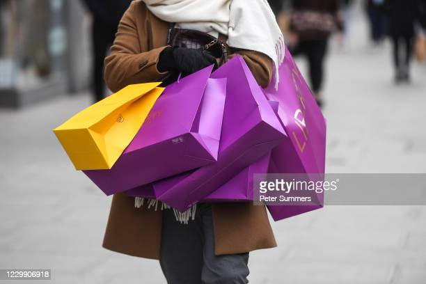 Man is seen carrying multiple shopping bags on Oxford Street on December 2, 2020 in London, England. Last night MPs voted in favour of government...