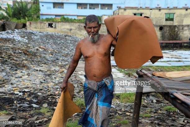Man is seen carrying tanned animal hides at a tannery in Hazaribagh, Dhaka. Most people in this area have become victims of pollution due to the...