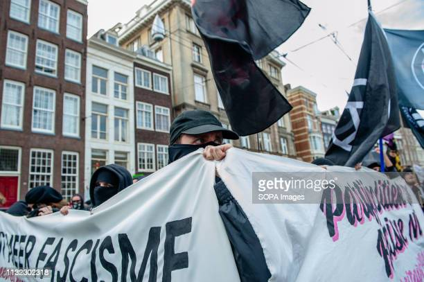 A man is seen covering his face while holding two Antifa big banners during the demonstration Thousands of people gathered at the Dam square in the...