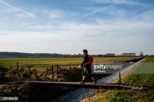 Man is seen crossing a small bridge, during the first weekend of warmer temperatures, in The Netherlands, on February 21st, 2021.