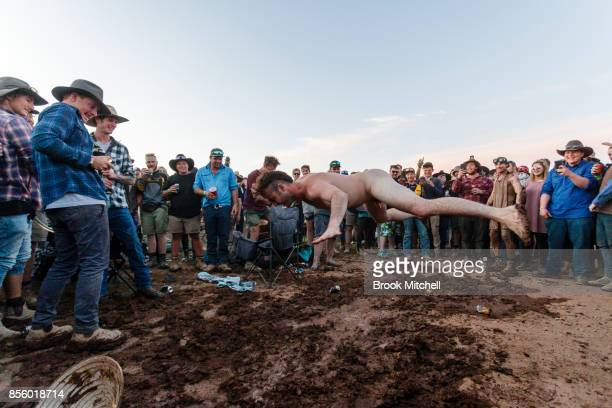A man is seen diving through the air into a makeshift mudpit on a wild final night at the 2017 Deni Ute Muster on September 30 2017 in Deniliquin...