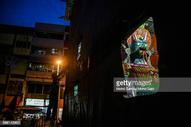 A man is seen do his work near the giant ghost during Hungry Ghost Festival on August 5 2016 in Kuala Lumpur Malaysia The Hungry Ghost Festival falls...