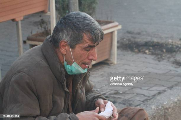 A man is seen effected from the tear gas smoke while demonstrators clash with riot police within antigovernment protests in Sulaymaniyah Iraq on...