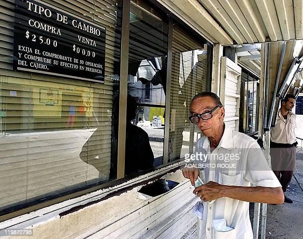 """Man is seen exchanging currency in La Habana, Cuba 23 October 2001. ACOMPANA NOTA: """" ECONOMIA DE CUBA SE DETERIORA TRAS IMPACTO DE ATENTADOS..."""
