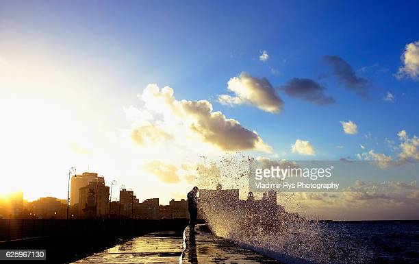 A man is seen fishing as a wave crashes on the Malecon promenade of city of Havana on November 06 2016 in Havana Cuba