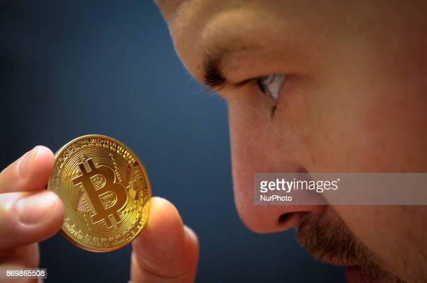 A man is seen holding a bitcoin replica on November 3 2017 Institutional inverstors are said to be warming to the bitcoin after it was announced CME...