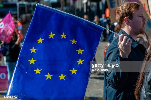 A man is seen holding a flag of the EU during the protest A day before the anniversary of the founding Treaty of the European Union citizens and...