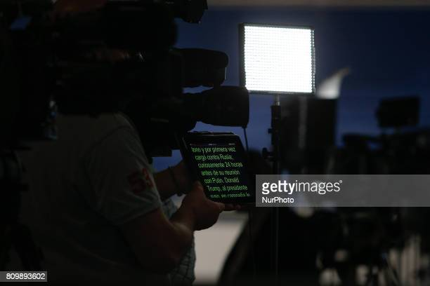 A man is seen holding a tablet scrolling text for a television reporter at the press center in the Hamburger Messe where the 2017 G20 meeting will be...
