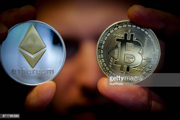 A man is seen holding replica cryptocurrency coins on November 8 2017