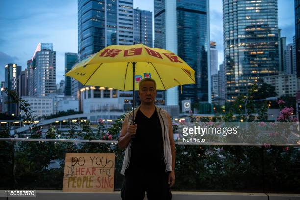 A man is seen holding up an yellow umbrella while standing next to a sign which reads Do You Hear the People Sing in Hong Kong China 18 June 2019