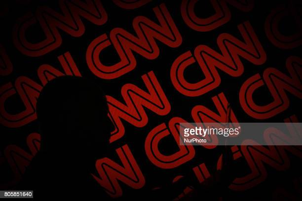 A man is seen holding with a smart device in front of a CNN logo in this photo illustration on 2 July 2017
