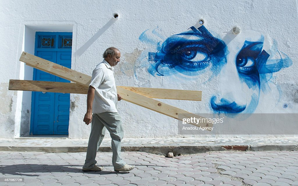 A man is seen in front of a wall with a three dimensional picture in Djerba island of Tunisia, on October 17, 2014. Three dimensional pictures painted by the 150 street performers from 30 countries attract tourist attention in Djerba, Tunisia. Pictures on the walls are about the Western and Islamic cultures as well as the developments in the world.